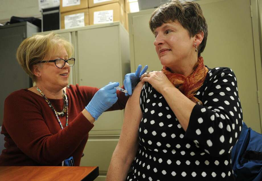 Public Health Nurse Kathy Malski, RN, gives a flu shot to Peggy Jo Thomas, of Morris, during a free flu shot clinic at Milford Health Department offices in Milford.