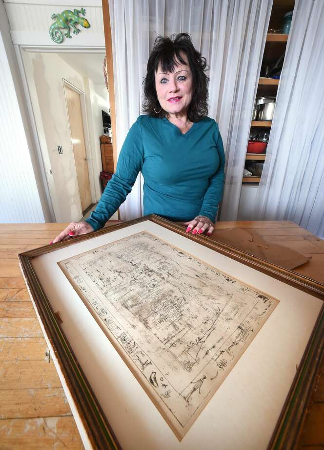 Cheryl Conroy Warren is photographed at her home in Milford with a signed etching titled, Flaura and Fauna, by Chinese artist Zao Wou-KI.