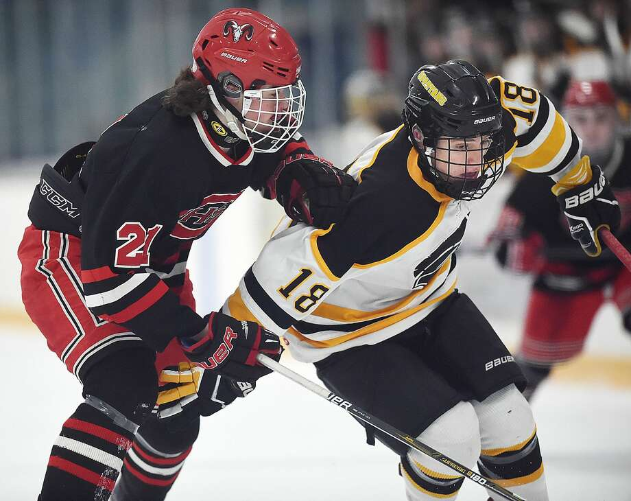 Amity junior forwared Jason Csejka and Cheshire junior defenseman James Ilnicki battle for the puck, Wednesday, Jan. 31, 2018, at Bennett Rink in West Haven. The Spartans tied the Rams, 4-4 in regulation, and a scoreless overtime.