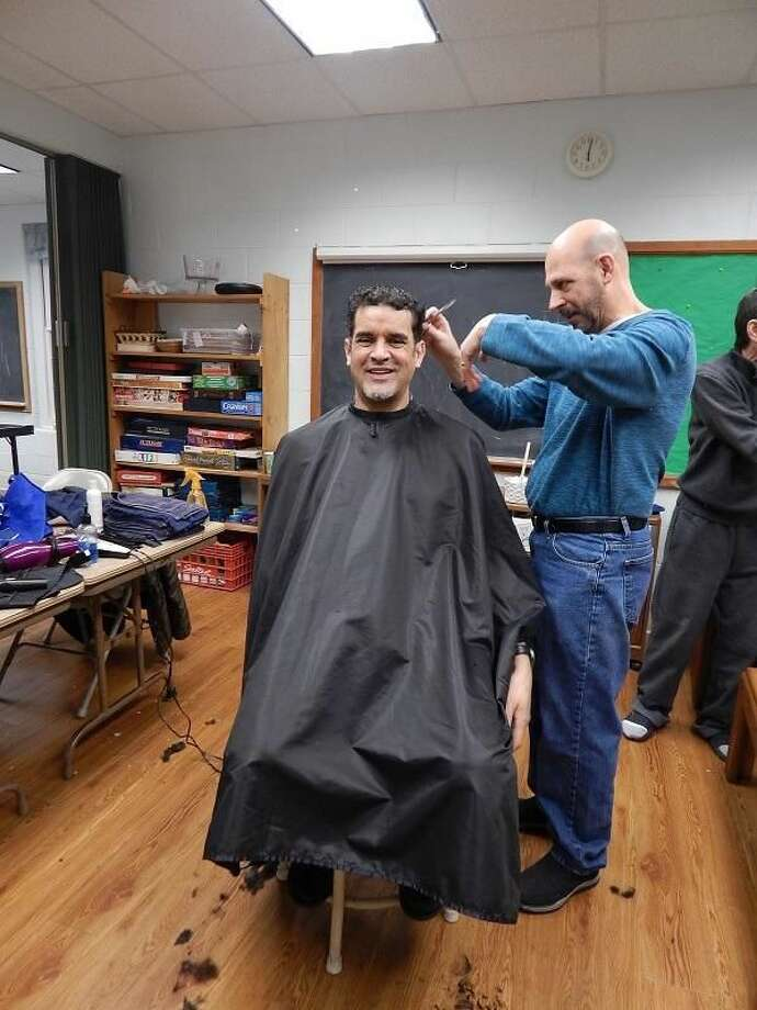 A resident of Columbus House has his hair cut by a volunteer barber as part of the Abraham's Tent program.