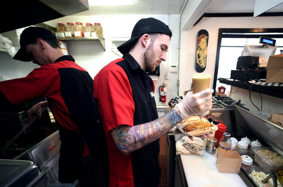 Bobby Manere Jr., adds mustard to a Yuppie Dog at Dogtown on New Haven Avenue in Milford.
