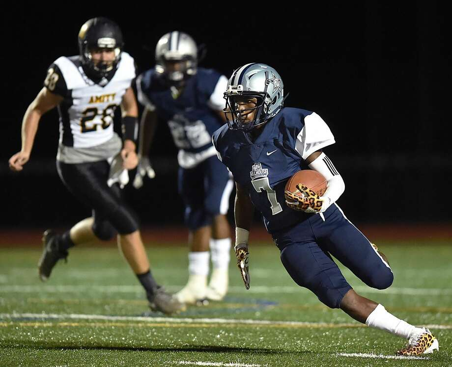 Hillhouse's Quintus Reid rushes the ball in the first half against Amity on Friday in New Haven.