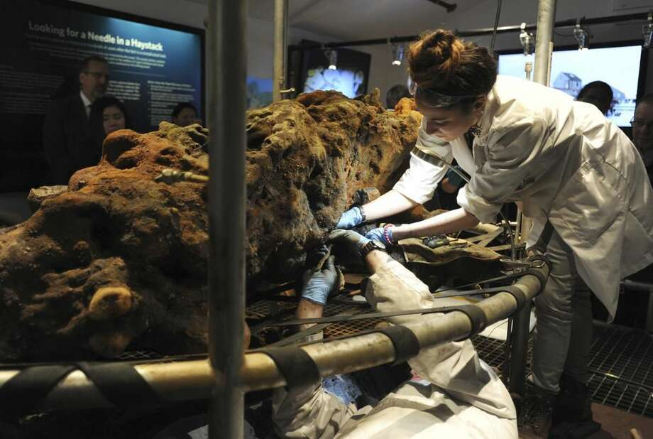 Christopher Macort, an underwater field archaeologist with the Whydah Pirate Museum, bottom, and Marie Kesten Zahn, an archaeologist and education coordinator at the Whydah Pirate Museum, remove what is believe to be a leg bone from a concretion in West Yarmouth.