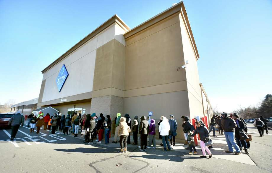 Shoppers stand in line outside of the entrance to Sam's Club in Orange on Jan. 14. The store is slated to close at the end of the month.