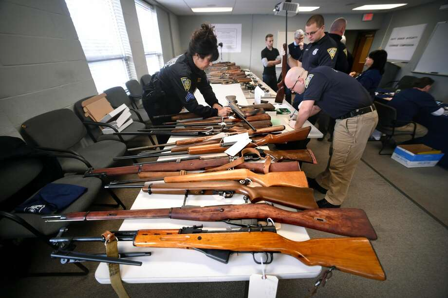 Sgt. Charlette Barham (left) and Detective Josh Kyle (right) catalogue rifles brought in during a gun buy-back at the New Haven Police Academy in New Haven.