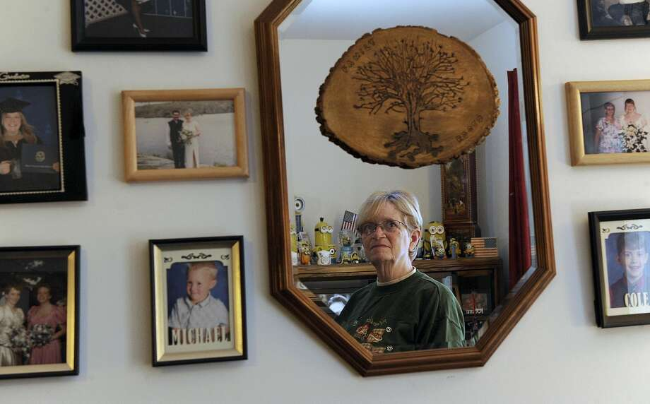 Kathy Sivertsen, 69, is the president of the resident association at Butter Brook Hill Apartments in New Milford, where many are concerned about the state budget. A hobby is geneology and she surrounds herself with family photos in her living room.