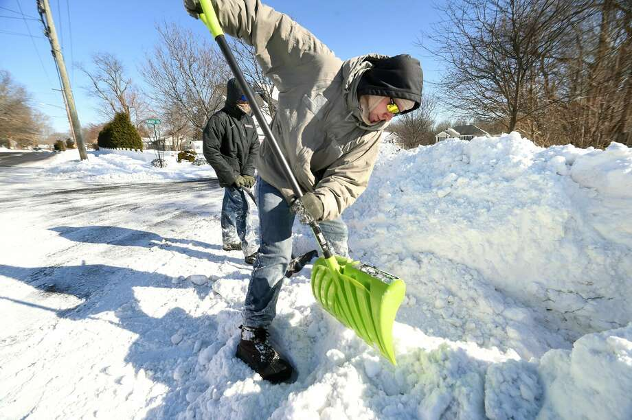 Isaac Bailey (left) and his brother, Stephen, shovel snow on a walkway at Calvary Alliance Church on Orange Ave. in Milford on Jan. 5.