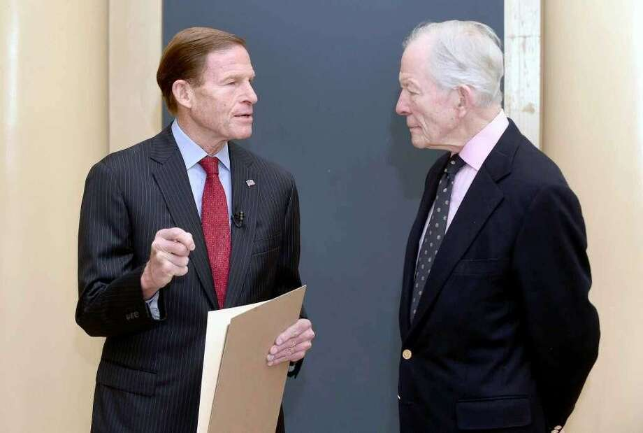 U.S. Senator Richard Blumenthal holds a resolution concerning a search for the San Antonio Rose B-17 Flying Fortress Heavy Bomber that went down during World War II in the Pacific Ocean and remains missing at Woolsey Hall in New Haven on November 10, 2017. At right is Doug Walker, son of Brigadier General Kenneth N. Walker, whose father was part of the crew of 11 aboard the plane when it went down under enemy fire.