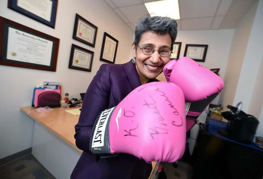 Dr. Anees Chagpar, Assistant Director of Global Oncology at the Yale Cancer Center, is photographed in her office in the Smilow Cancer Hospital with a pair of boxing gloves she received from the Soho Hair Salon when she began work in New Haven.