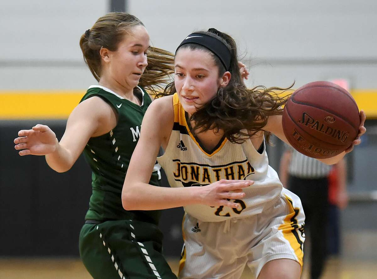 Law senior captain Colleen Goodwin drives around Maloney sophomore Olivia Aitken in the fourth quarter of their Class L first-round matchup Tuesday at Jonathan Law High School in Milford. The Lady Lawmen beat Maloney, 62-28.