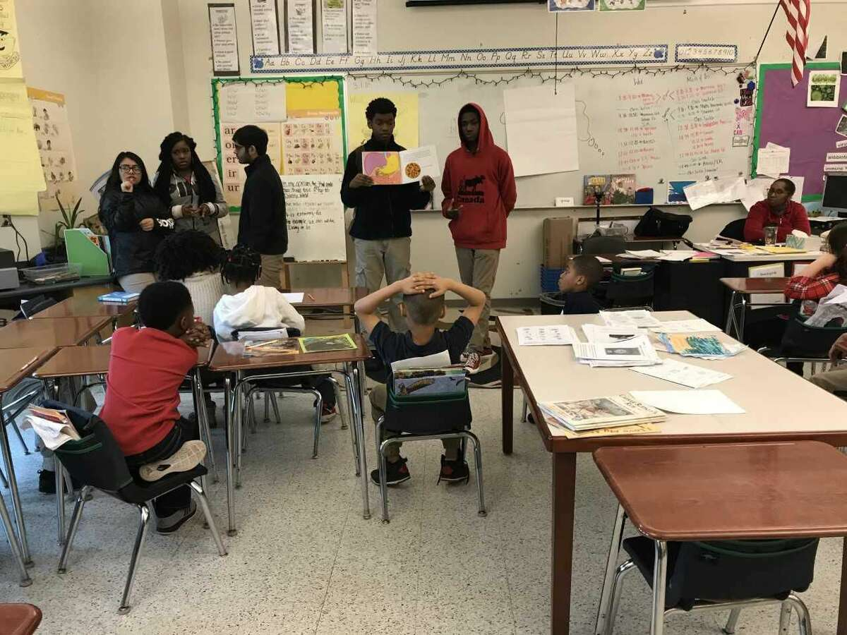 Creed High School sophomores Ssanyu Rogers and Jamar Crawford show Celentano third-graders a diagram of the human digestive system.