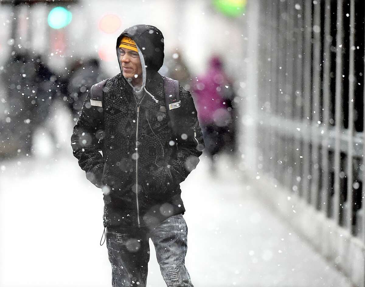 A man walks on Church Street in New Haven during the nor?'easter, Wednesday, March 7, 2018, a winter storm predicted to bring four to eight inches of snow in the New Haven area.