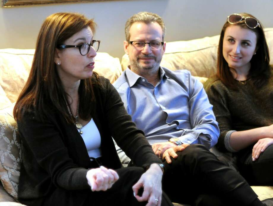 State Sen. Gayle Slossberg (D-14th Dist.), left, announces that she will not seek re-election after 14 years during an informal gathering at her home in Milford. Seated with Gayle is her husband David and daughter Rebecca.