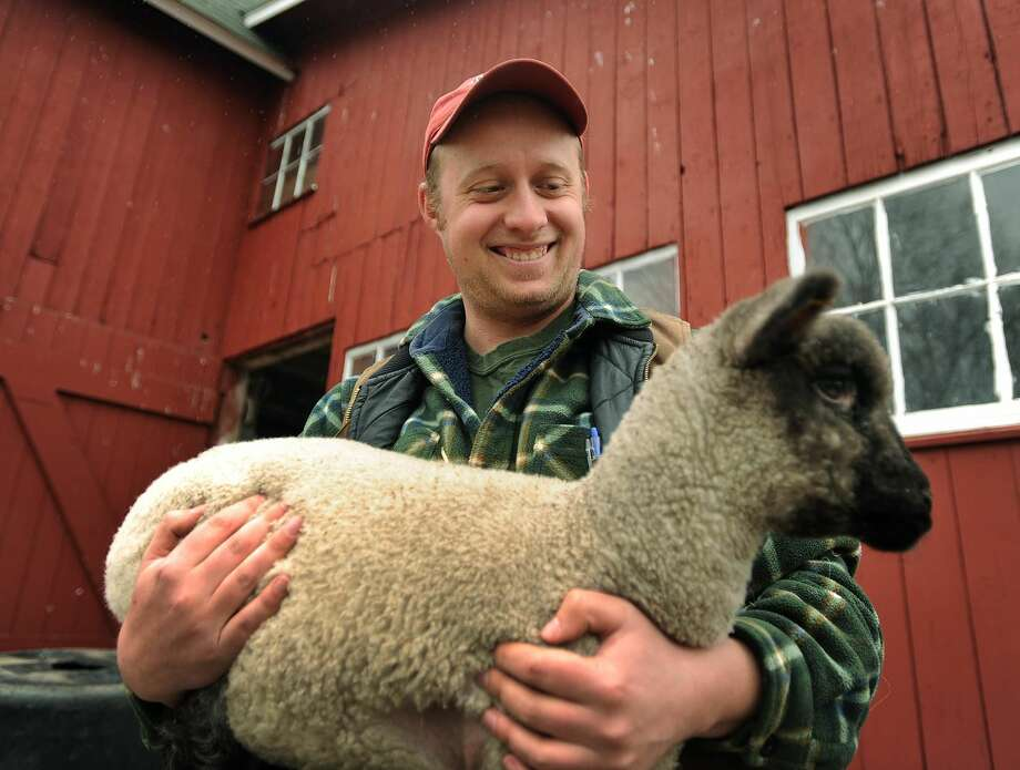 Lars Demander holds a Shropshire lamb at his family's Clover Nook Farm in Bethany, Conn. on Thursday, March 29, 2018. Demander was recently named Connecticut's Outstanding Young Farmer for 2018 by the Connecticut Agricultural Information Council.