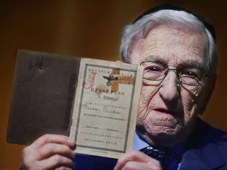 New Haven resident and Holocaust survivor Isidor Juda, 96, holds his passport at the Holocaust Remembrance Day at Bucknall Theater at the University of New Haven.