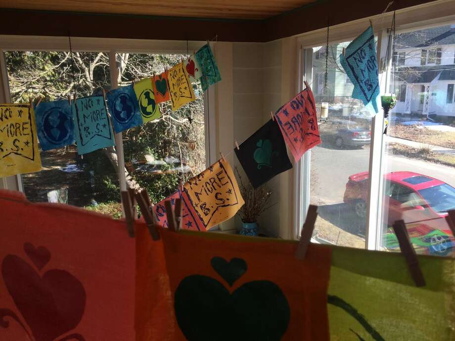 Three Westville women are hanging flags around New Haven promoting unity and peace. These are hanging inside Tina Santoni's sunroom.