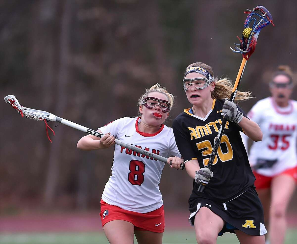 Foran's Emily Kwalek, left, chases Amity's Ana Carney during Thursday's game in Milford.