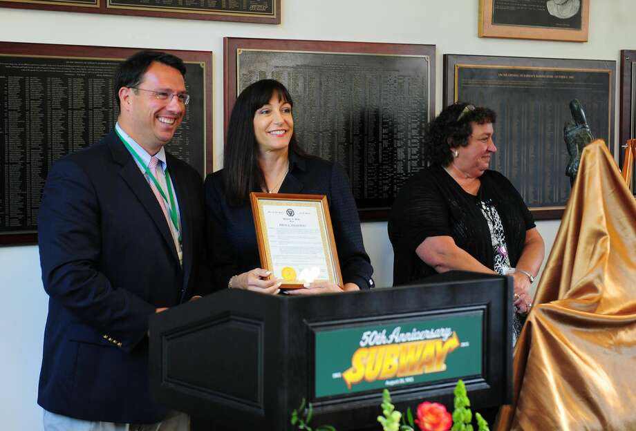 Milford Mayor Ben Blake presents a proclamation to Subway CEO Suzanne Greco at its 50th anniversary celebration at the world headquarters in Milford, on Aug. 27, 2015.