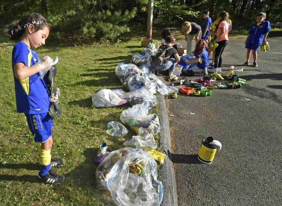 Lilly Montiel, 8, of Woodbridge at The Everson Soccer Club of Woodbridge with teammates, parents and coaches, with the collection of soccer cleats and soccer equipment that will be sent to Brazilian children in need with the assistance of Cleats For Dreams.