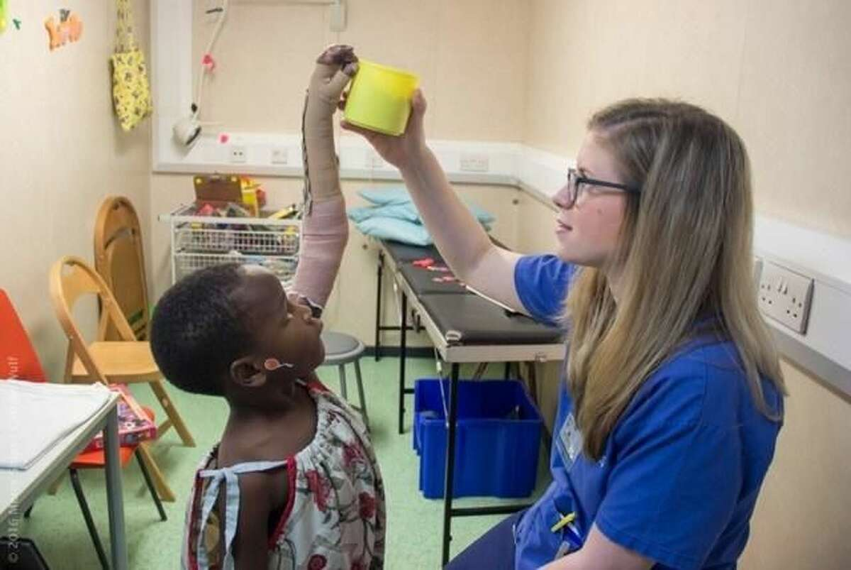 Elisabeth Mordecai, an occupational therapist with a specialty in hands, treats a burn victim aboard a hospital ship in Africa.