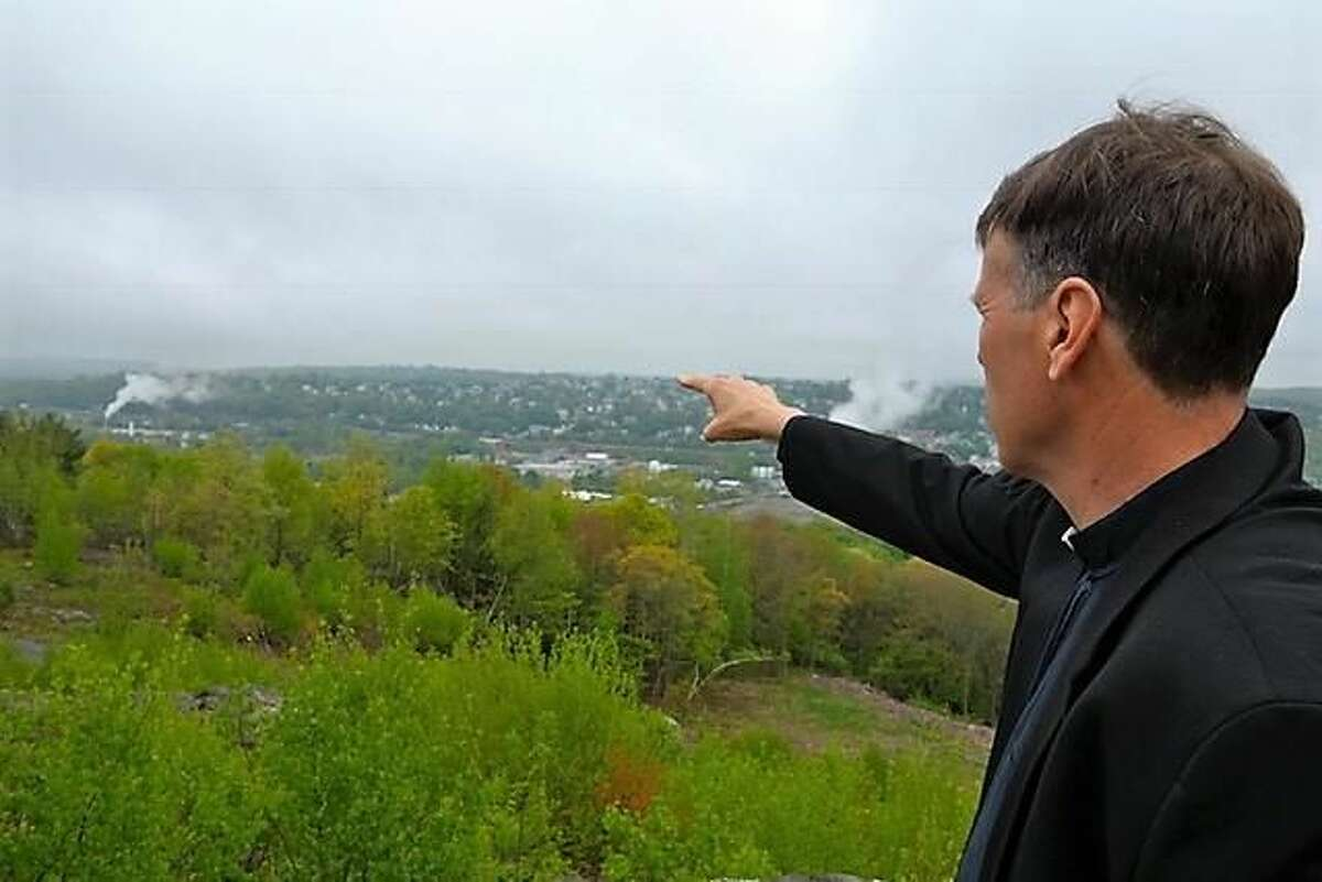 Fr. James Sullivan points to the place where Venerable Fr. Michael McGivney, founder of the Knights of Columbus, was born near the Naugatuck River in Waterbury.