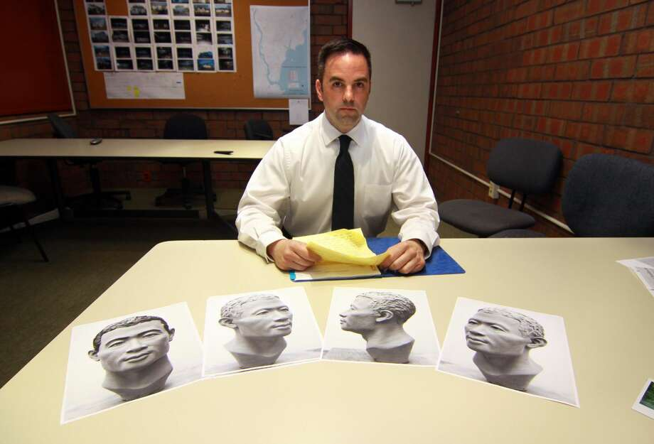Milford Police Department's Detective Mitchell Warwick, who is responsible for two cold cases, poses at police headquarters in Milford. The photos in front of Det. Warwick depict the reconstructed face made from a skull.