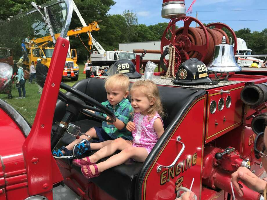 Two-year-old twins Eric and Victoria Sauter at the wheel of a firetruck.