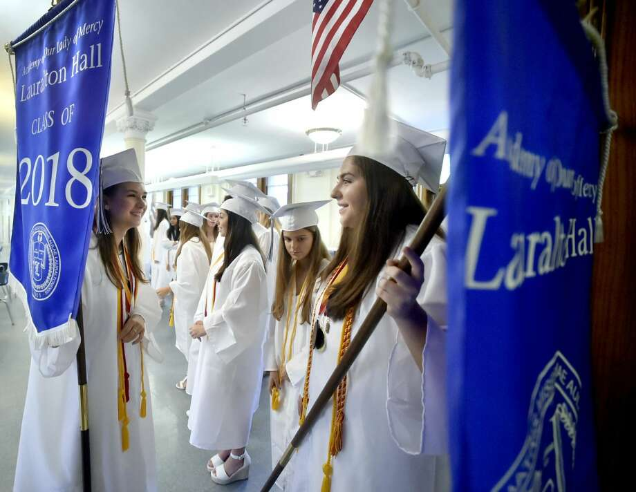 Lauralton Hall Salutatorian Lily Wald of Derby, left, and Valedictorian Caroline Favano of Norwalk, right, hold on to Lauralton Hall banners as the wait to lead the Lauralton Hall Class of 2018 Graduation processional Saturday.
