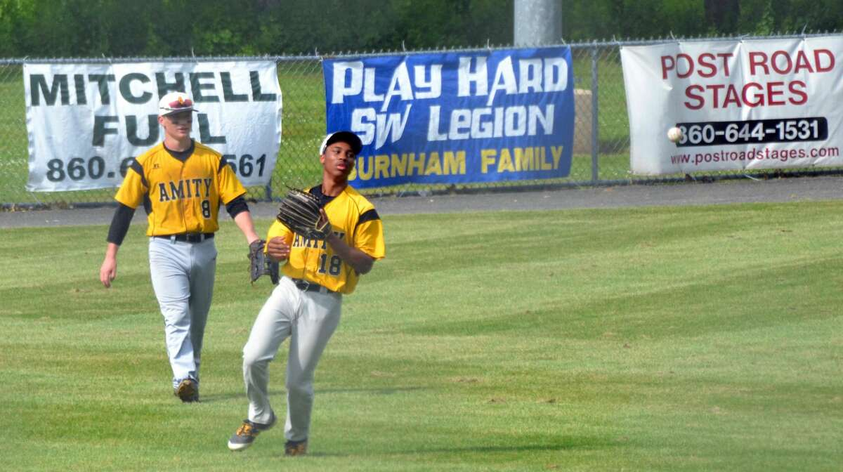 Amity's Julian Stevens flips the ball into the infield after making a catch against South Windsor in the Class LL quarterfinals on Saturday.