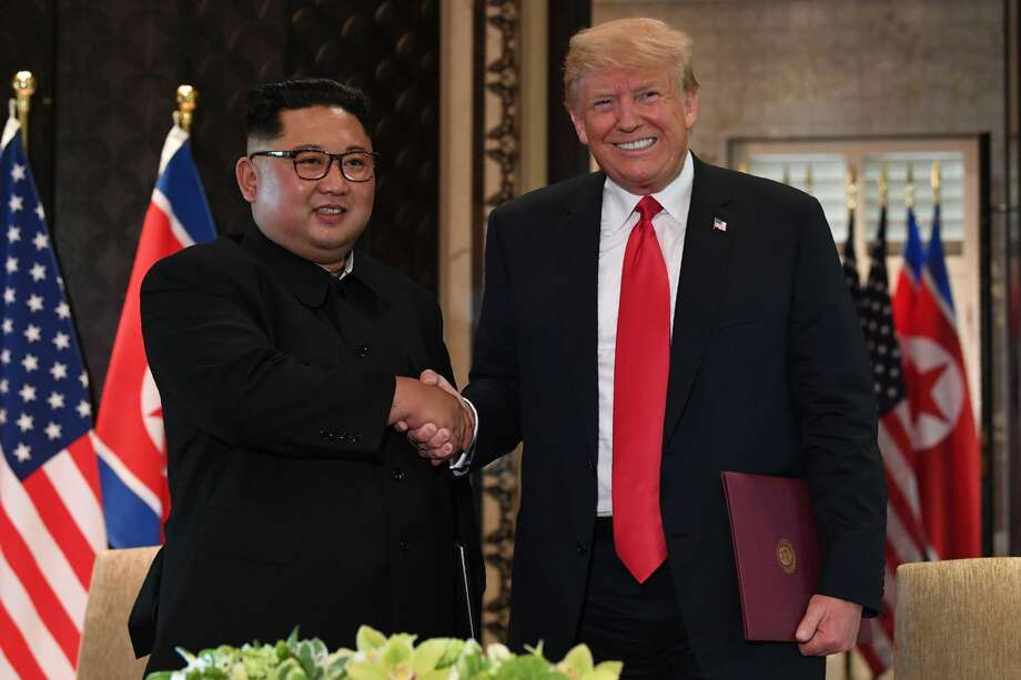 US President Donald Trump (R) and North Korea's leader Kim Jong Un shake hands following a signing ceremony during their historic US-North Korea summit, at the Capella Hotel on Sentosa island in Singapore on June 12, 2018. Donald Trump and Kim Jong Un became on June 12 the first sitting US and North Korean leaders to meet, shake hands and negotiate to end a decades-old nuclear stand-off.