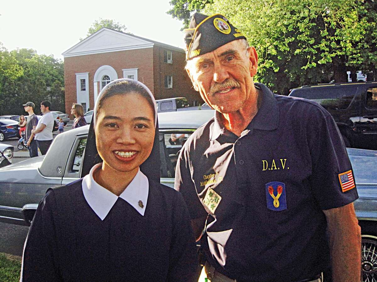 Sister Oanh Nguyen, left, and writing group member, Vietnam veteran Jerry Augustine; posed for a photograph after she brought along other Holy Apostles students to share their experiences in their homeland this week at the library.