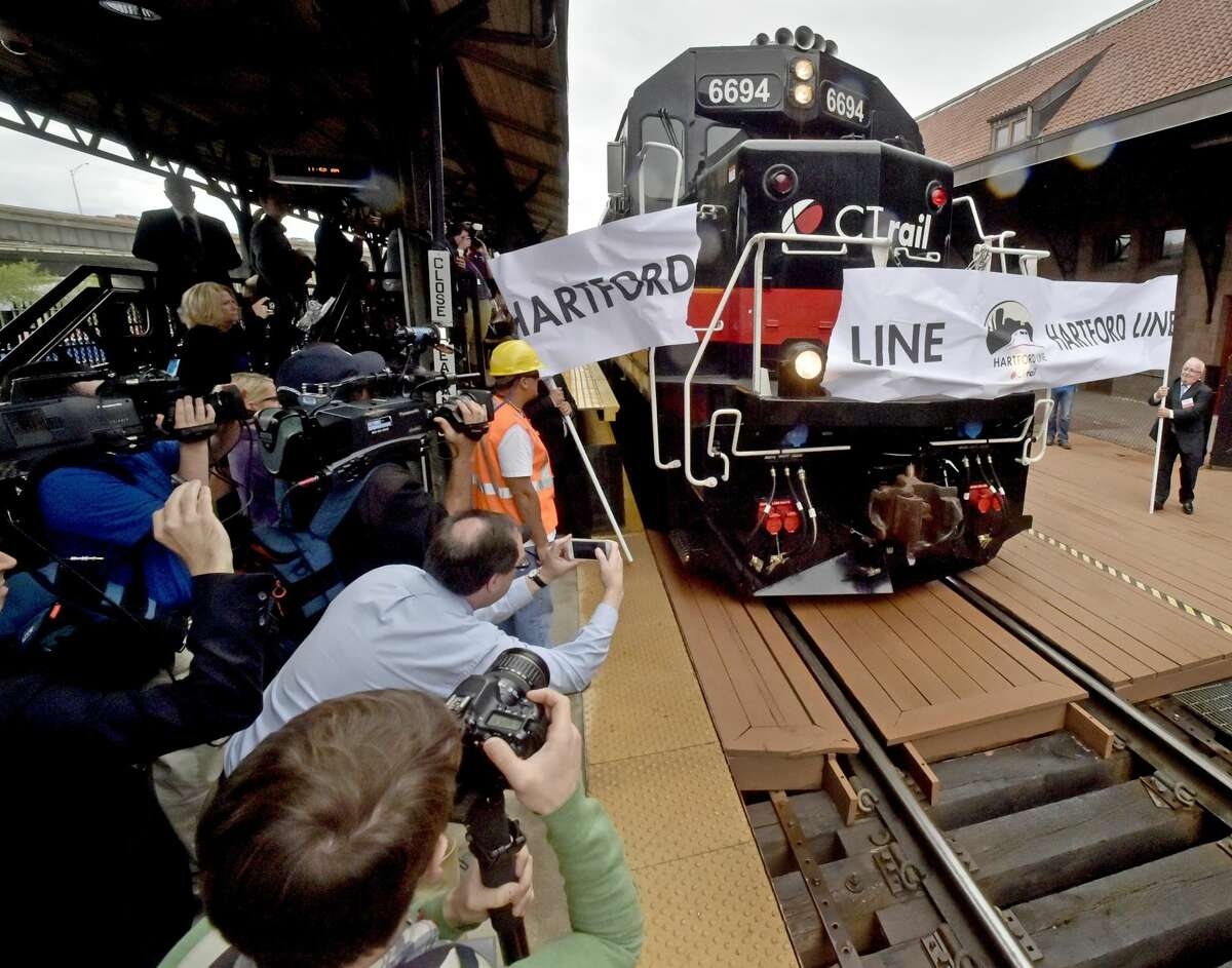 The CTrail Springfield train arrives in Hartford, breaking a paper banner heralding the inaugural run of the new CTrail Hartford Line Connecticut Rail commuter service launched in June with frequent train service between New Haven, Hartford and Springfield.