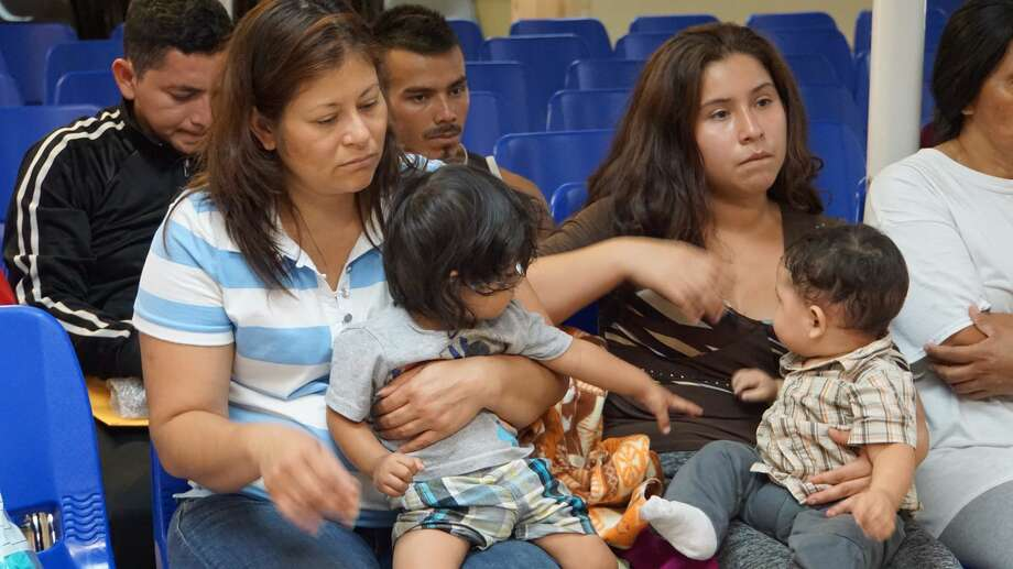 Mothers and children wait to be assisted by volunteers in a humanitarian center in the border town of McAllen, Texas on June 14, 2018.