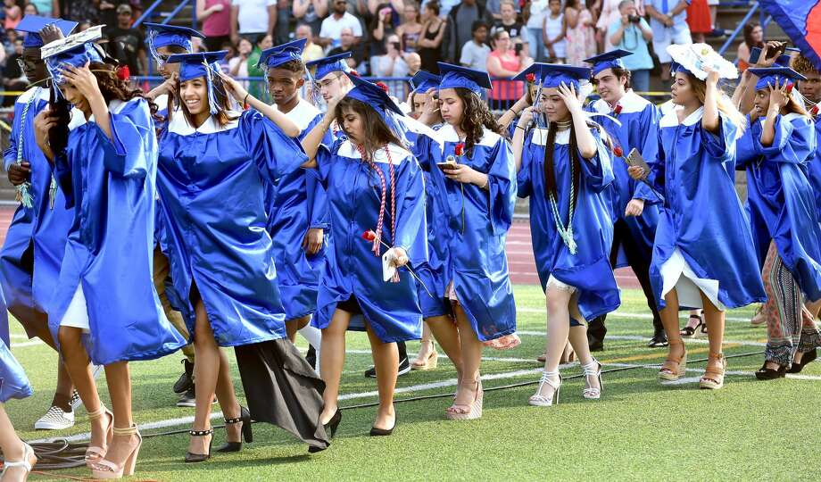 Graduates hold onto their caps as a gust of wind passes as they enter the football field for graduation at West Haven High School.