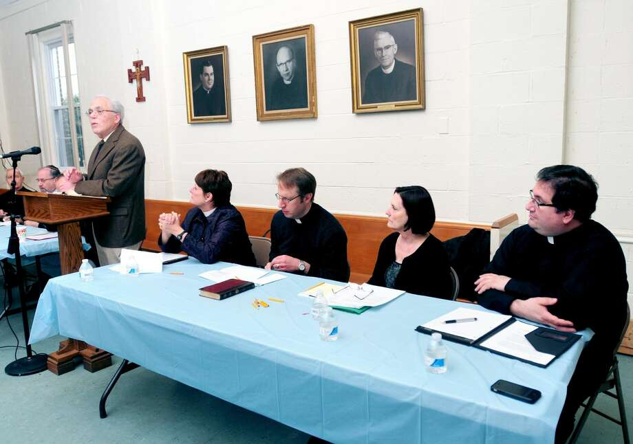 Dr. Julius Landwirth (left) speaks at a forum on physician-assisted dying at the Holy Infant Roman Catholic Church in Orange on March 30, 2014. Members of the Orange clergy seated left to right are Rev. Ann Ritonia of the Church of the Good Shepherd, Rev. Tim Boerger of Ziion Lutheran Church, Rev.Suzanne Wagner of Orange Congregational Church and Father Peter Orfanakos of St. Barbara Greek Orthodox Church.