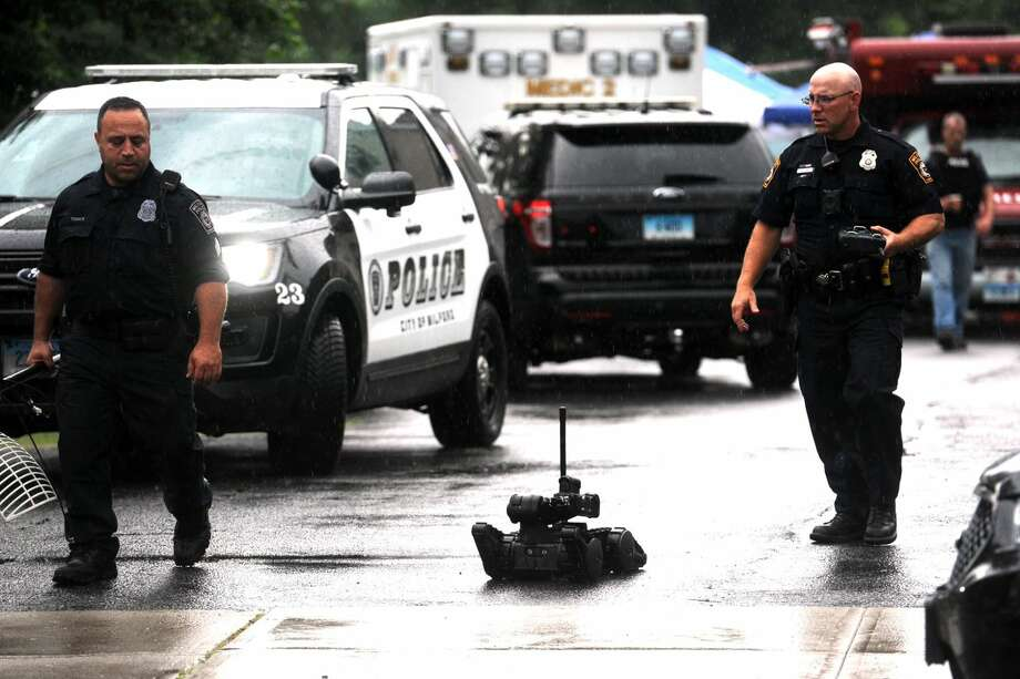 Milford Police officers leave the scene with a robot after a man was taken into custody after barricading himself inside a residence in the Beaver Brook Gardens condominiums in Milford Friday morning. After a lengthy standoff with police, the man finally gave himself up without incident.