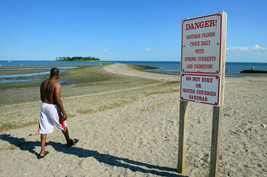 Several signs warn people about the tombolo, or sandbar, that leads to Charles Island at Silver Sands State Park in Milford. The signs have been posted to warn people about the dangers of using the land bridge which is covered by the tides on a daily basis.