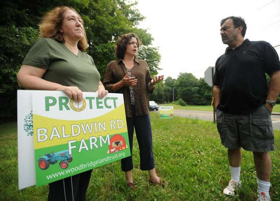 From left; Woodbridge Land Trust members Cynthis Anger, Cathy Wick, and Bryan Pines by the 86-acre Baldwin Road Farm property in Woodbridge. The trust is looking to preserve the property in perpetuity as farmland by purchasing the development rights.