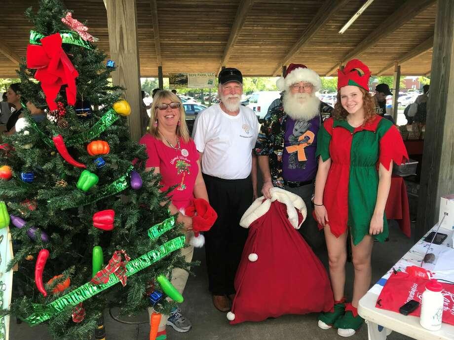 Walnut Beach Farmers Market celebrates Christmas in July with Market Master Meta Carter, Walnut Beach Arts and Business Association President Gary Dangle, Santa Claus (Rick George) and Elf Anna Downs.