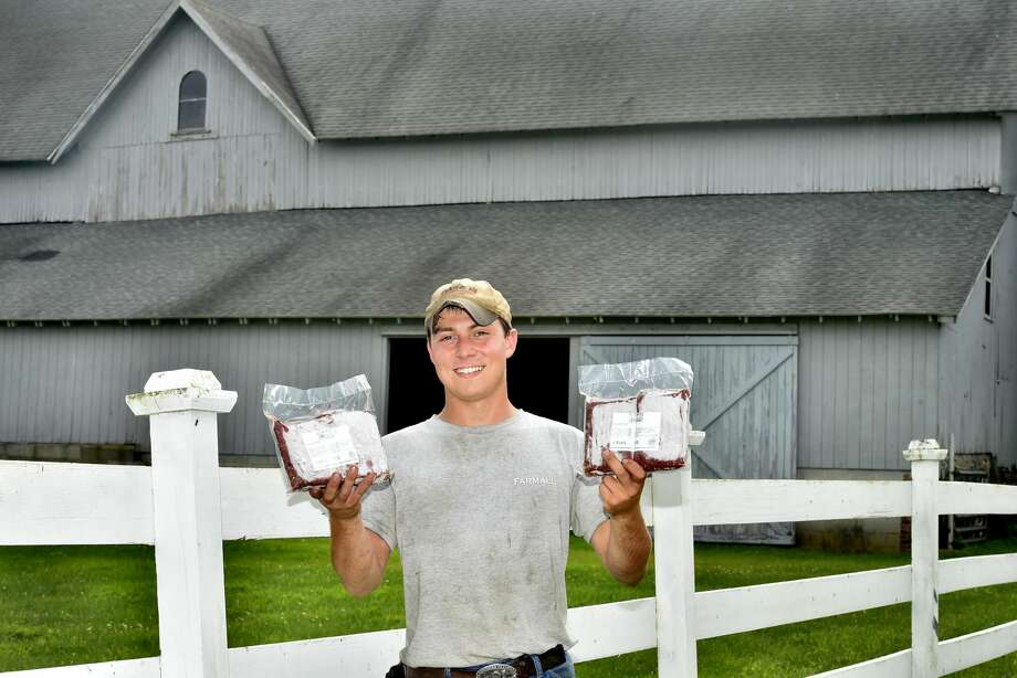 Cristian Mortali of Orange, a former employee of Shamrock Farm in Orange, holds frozen cryovac packages of USDA inspected organic beef from Hereford and Simmental Cattle at Jim Zeoli's Shamrock Farm in Orange.