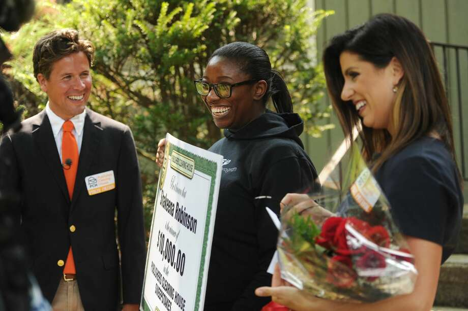 Shakeena Robinson, center, of Milford, is surprised by Publishers Clearing House Prize Patrol members Howie Guja, left, and Danielle Lam with a ten thousand dollar prize at her home.