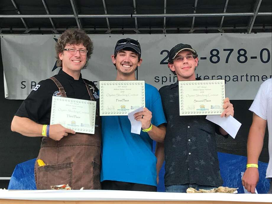 Honor Allen, center, first place winner in the Oyster Shucking Contest at the Oyster Festival, with second and third place winners Ed Nead, right, and Eli Carter, left.