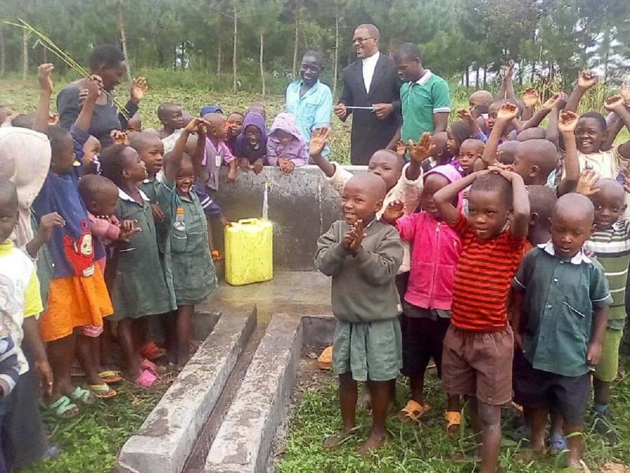 Children in Ugandan village are all smiles over the arrival of water.