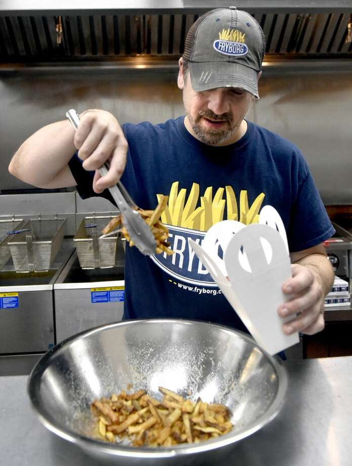 Jonathan Gibbons, owner of Fryborg in Milford, an eclectic eatery featuring hand-cut french fries as the main attraction, with variation of flavorings and dipping sauces on a menu that also includes sandwiches, prepares a serving of french fries.