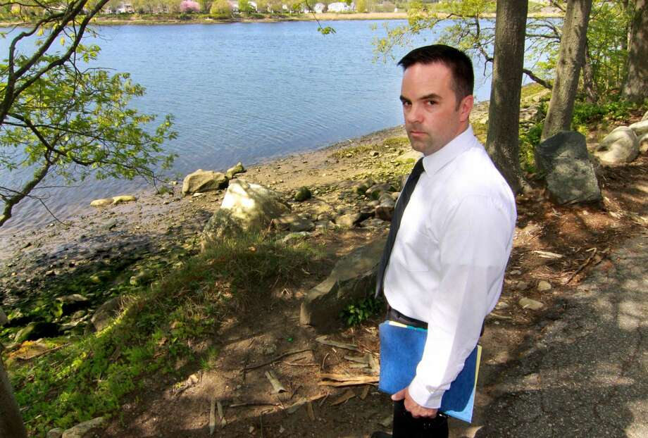 Milford Police Department's Detective Mitchell Warwick, who is responsible for two cold cases, stands near the scene of one of them on Old Oronoque Road in Milford. On March 24, 1994, public works came across a military-style duffle back near the Housatonic River off the side of Old Oronoque Road in Milford. Inside the bag, they found a man's torso.