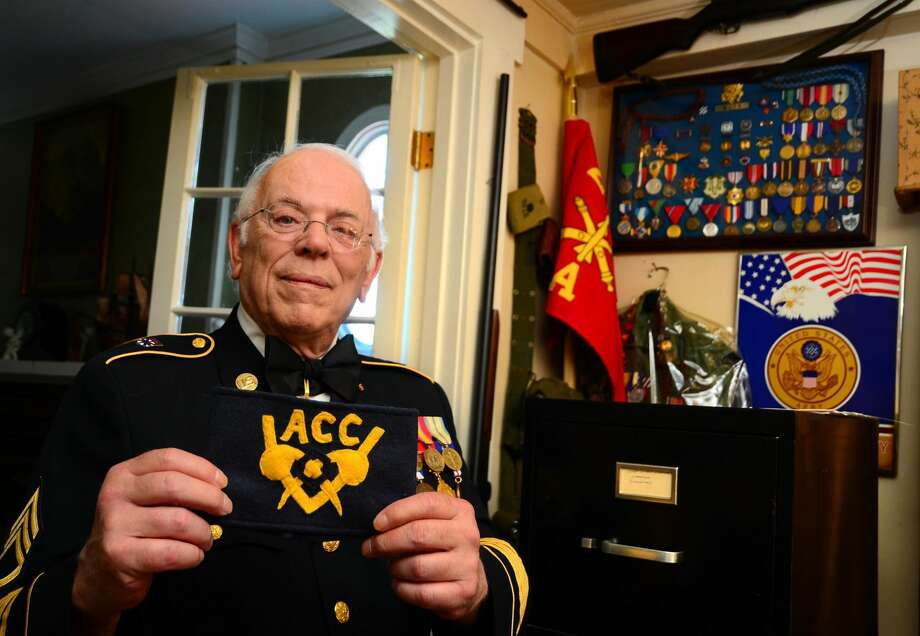 Retired Army Staff Sergeant Eric Muth with an Army Chemical Corps arm band at his home in Milford. Muth was a volunteer for the special banch during the Cold War era. Muth recently donated a trove of documents and other related material to the army's military museum.