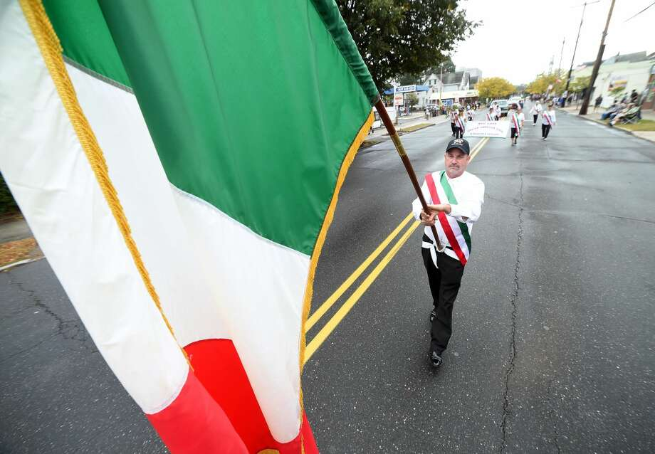 Paul Frosolone, president of the West Haven Italian American Club, carries the Italian flag up Campbell Ave. during the Greater New Haven Columbus Day Parade in West Haven on Oct. 8, 2017.
