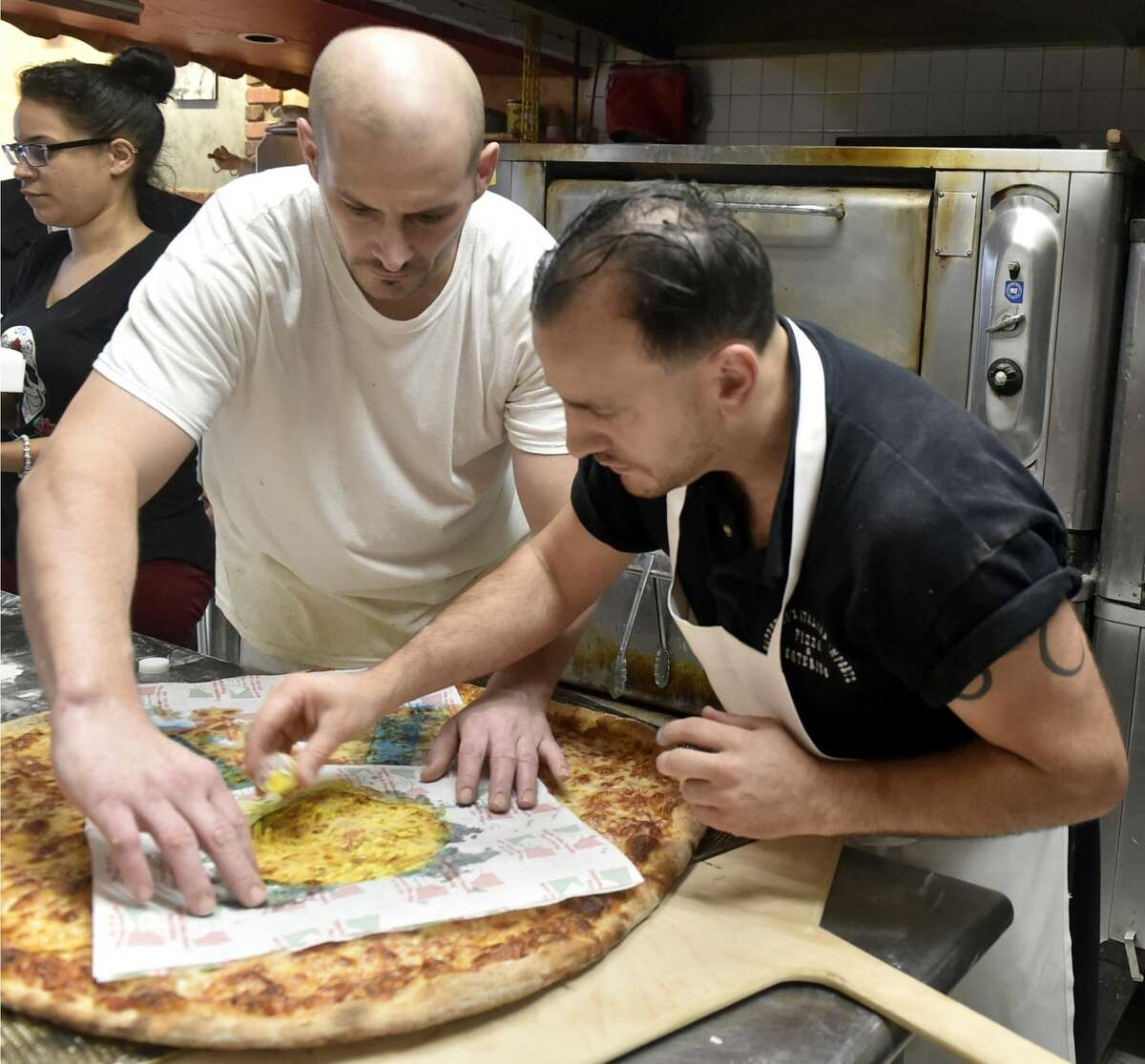 Pizza maker Chris Stackpole, left, and his boss Donato Cappetta, owner of Cappetta's Italian Imports, Pizza and Catering in West Haven, make a giant, 30-inch round pizza with an eatable blue-and-gold ribbon on top to honor nearby Forest School for being named as just one of four national Blue Ribbon Schools in Connecticut.