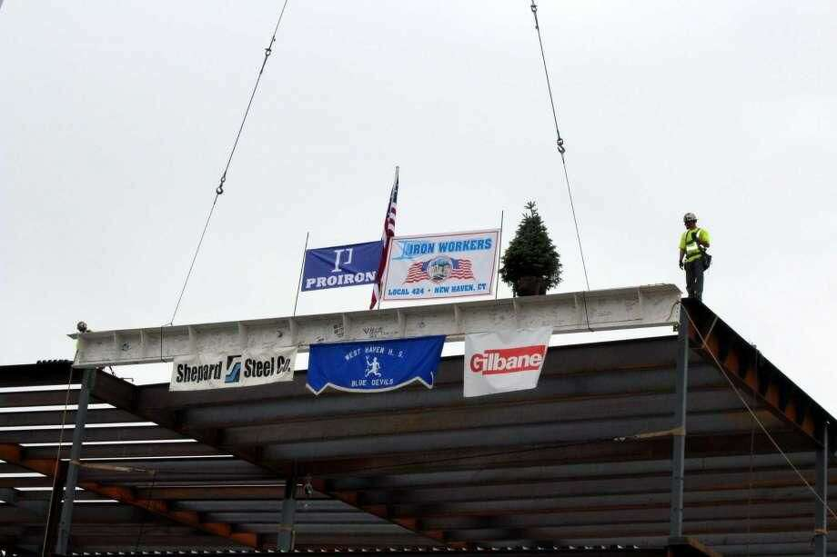 "A signed I-beam is hoisted by a large crane and set by two iron workers atop West Haven High School's future media center during a ""topping-off"" ceremony on Thursday, Oct. 11, to celebrate completion of the steel framework for the addition portion of the school's $130 million reconstruction and renovation project."