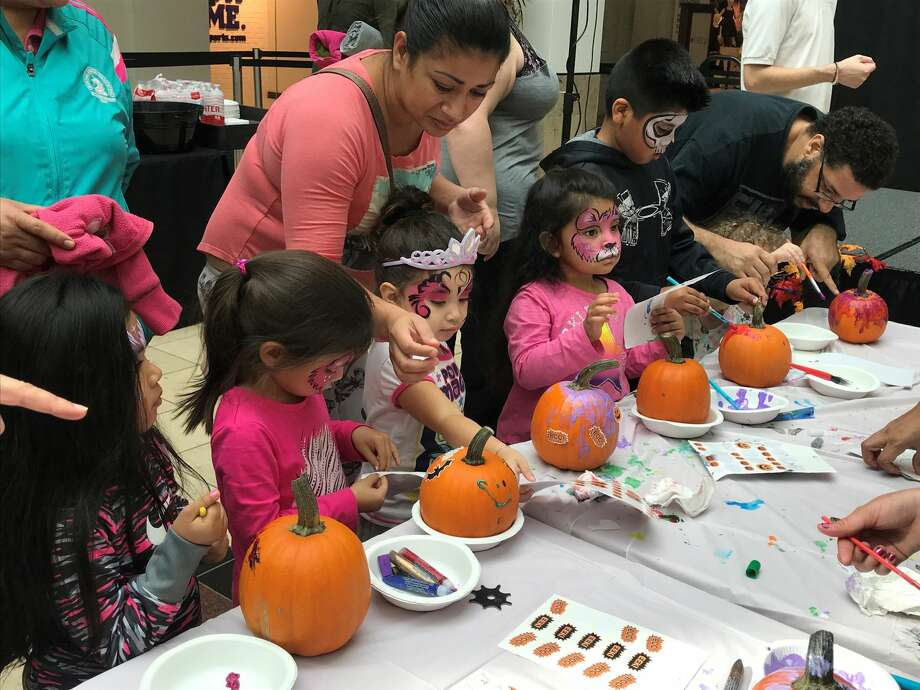 Kids decorate pumpkins to get into the holiday spirit.